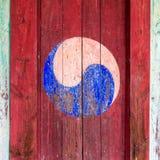 Eum y Yang Symbol, variante coreana de Yin y de Yang Pintura retra colorida con el fondo rojo en una puerta de madera imágenes de archivo libres de regalías