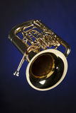 Euphonium tuba Isolated on Blue. A gold brass tuba euphonium baritone horn isolated against a spotlight blue background in the vertical format Stock Images