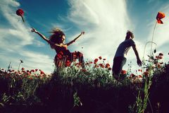 Euphoria. man and girl in red poppy field. Euphoria. men and girl with long curly hair in red dress with flower bouquet dancing in field of poppy seed with green stock photography