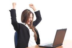 Euphoric affärskvinna som håller ögonen på en bärbar dator Arkivfoto