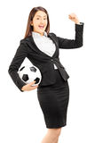 Euphoric businesswoman holding a soccer ball and gesturing Stock Image