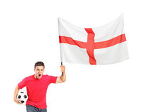 Euphoric fan holding a ball and English flag. An euphoric fan holding a soccer ball and English flag isolated on white background Royalty Free Stock Photography