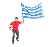 Euphoric fan holding a ball and flag. Full length portrait of an euphoric fan holding a ball and flag of Greece  on white background Stock Image