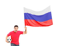 An euphoric fan holding a ball and a russian flag. An euphoric fan holding a ball and waving a russian flag isolated on white background Royalty Free Stock Photo