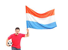 Euphoric fan holding a ball and waving a flag. An euphoric fan holding a ball and waving a dutch flag isolated on white background Royalty Free Stock Image