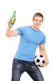 An euphoric fan holding a beer bottle and football cheering. Isolated on white background Stock Photos
