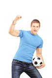 Euphoric fan holding a soccer ball and cheering Stock Image