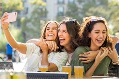 Euphoric girl friends taking selfie together on terrace. royalty free stock images