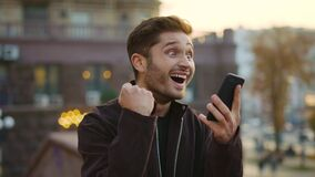 Euphoric guy receiving message phone outdoors. Excited man gesturing like winner