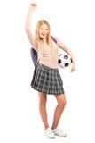 Euphoric kvinnlig deltagare med ryggsäckinnehav som en fotboll klumpa ihop sig Royaltyfri Bild