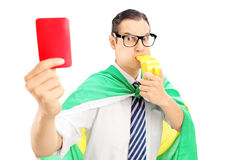 Euphoric male fan with flag holding a red card and blowing a whi Royalty Free Stock Photos