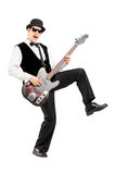 Euphoric man playing a bass guitar. Full length portrait of an euphoric man playing a bass guitar isolated on white background Stock Images