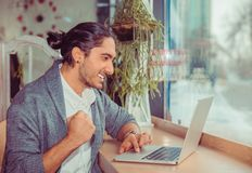Euphoric man pumping fist while looking at the laptop stock photos