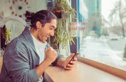 Euphoric man pumping fist while looking at mobile smartphone stock photography