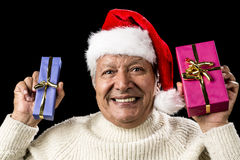 Euphoric Old Man With Two Presents And Santa Hat. Excited male senior advertising a wrapped present in each raised hand. One blue and the other magenta. Both Stock Photography