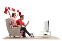 Euphoric soccer fans watching football on television. Isolated on white background Stock Photos