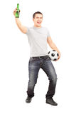 Euphoric sport fan holding a beer bottle and football. Full length portrait of an euphoric sport fan holding a beer bottle and football cheering  on white Royalty Free Stock Photography