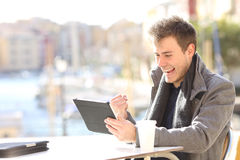 Euphoric winner winning and watching a tablet. Handsome euphoric winner winning and watching a tablet in a coffee shop terrace of a port of urbanization with the Royalty Free Stock Image