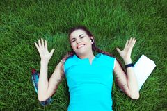 Euphoric woman hands in air happy gesture lying down stock photo