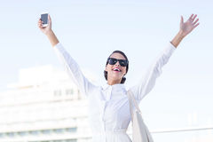 Euphoric woman holding smartphone with hands up. Outside Stock Photography