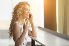 Euphoric woman searching job in cafe. Beautiful girl is talking on the phone and happy with the good news. Royalty Free Stock Image
