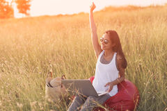 Euphoric woman searching job with laptop in a meadow Royalty Free Stock Photo