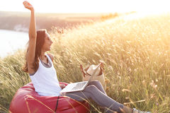 Euphoric woman searching job with a laptop in outdoors. Happy girl winner in meadow at sunrise with copy space Stock Image