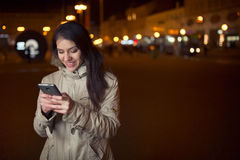 Euphoric woman using her smart phone and smiling to good news message.Happy woman typing text message on a smart phone Royalty Free Stock Photos