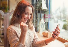 Euphoric woman watching her smart phone stock photography