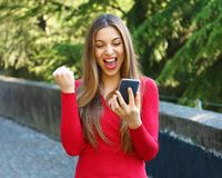 Euphoric woman watching her smart phone outdoor stock image
