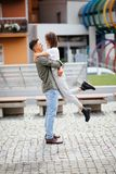 Euphoric young couple meeting and hugging on the street. Smiling couple in love standing on the street summer royalty free stock image