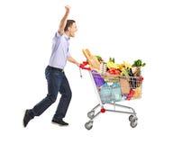 Euphorischer Mann, der einen Einkaufswagen drückt Stockfotos