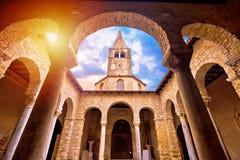 Euphrasian Basilica in Porec arcades and tower sun haze view. UNESCO world heritage site in Istria, Croatia royalty free stock photo
