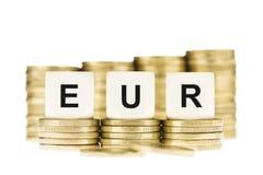 EUR (eurovaluta) på bunten för guld- mynt som isoleras på vit Fotografering för Bildbyråer