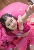 Eurasian girl catching bubbles. Royalty Free Stock Photography