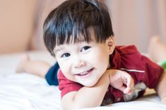 Eurasian toddler boy smiling on a bed. Stock Photos