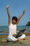 Eureka on the beach. Asian boy with laptop computer on tropical pristine beach amazed with the hands in the air, shouting victory. Concept of success and royalty free stock photo
