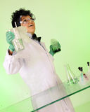 Eureka!. A young `mad scientist` happily displaying two volatile solutions -- one green and bubbly, the other clear and steamy Royalty Free Stock Photos