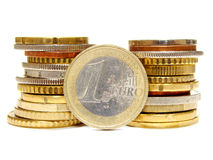 Euro. A single Euro coin leaning on two stacks of coins, isolated on white Royalty Free Stock Image