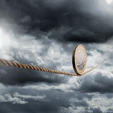 Euro. Coin balancing on a tightrope