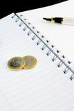 Euro affaires de pièce de monnaie sur le bloc-notes Photographie stock libre de droits