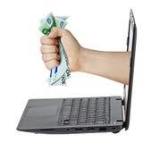 Euro afferrante dei soldi della mano del computer portatile isolato Fotografia Stock Libera da Diritti