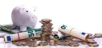 Euro banconote acciambellate ed euro monete al porcellino salvadanaio bianco della moneta di posizioni differenti immagine stock