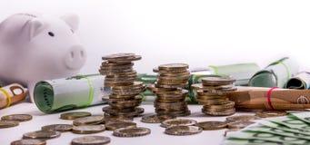 Euro banconote acciambellate ed euro monete al porcellino salvadanaio bianco della moneta di posizioni differenti immagini stock