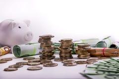 Euro banconote acciambellate ed euro monete al porcellino salvadanaio bianco della moneta di posizioni differenti fotografie stock libere da diritti