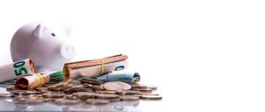 Euro banconote acciambellate ed euro monete al porcellino salvadanaio bianco della moneta di posizioni differenti fotografie stock