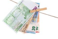 Euro banconote che appendono sulla corda da bucato su fondo bianco Fotografie Stock