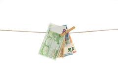 Euro banconote che appendono sulla corda da bucato su fondo bianco Immagine Stock Libera da Diritti