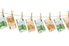 Euro banconote che appendono sulla corda da bucato su fondo bianco Fotografia Stock