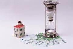 EURO banconote e una casa del giocattolo e della clessidra su un fondo bianco Il tempo è denaro concetto Immagine Stock